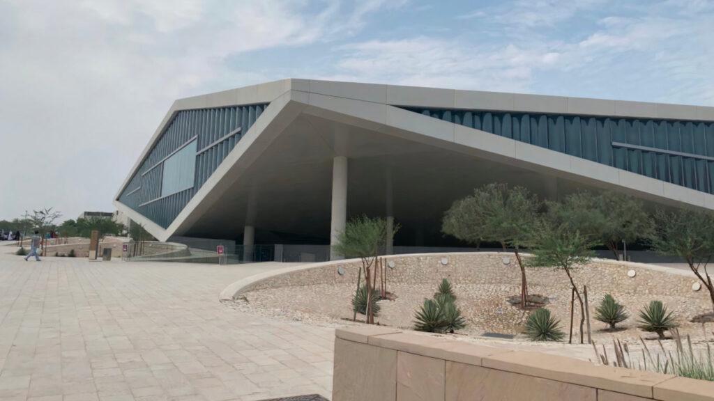 Entrada da Biblioteca. edifício moderno rodeado de algumas plantas e arbustos.