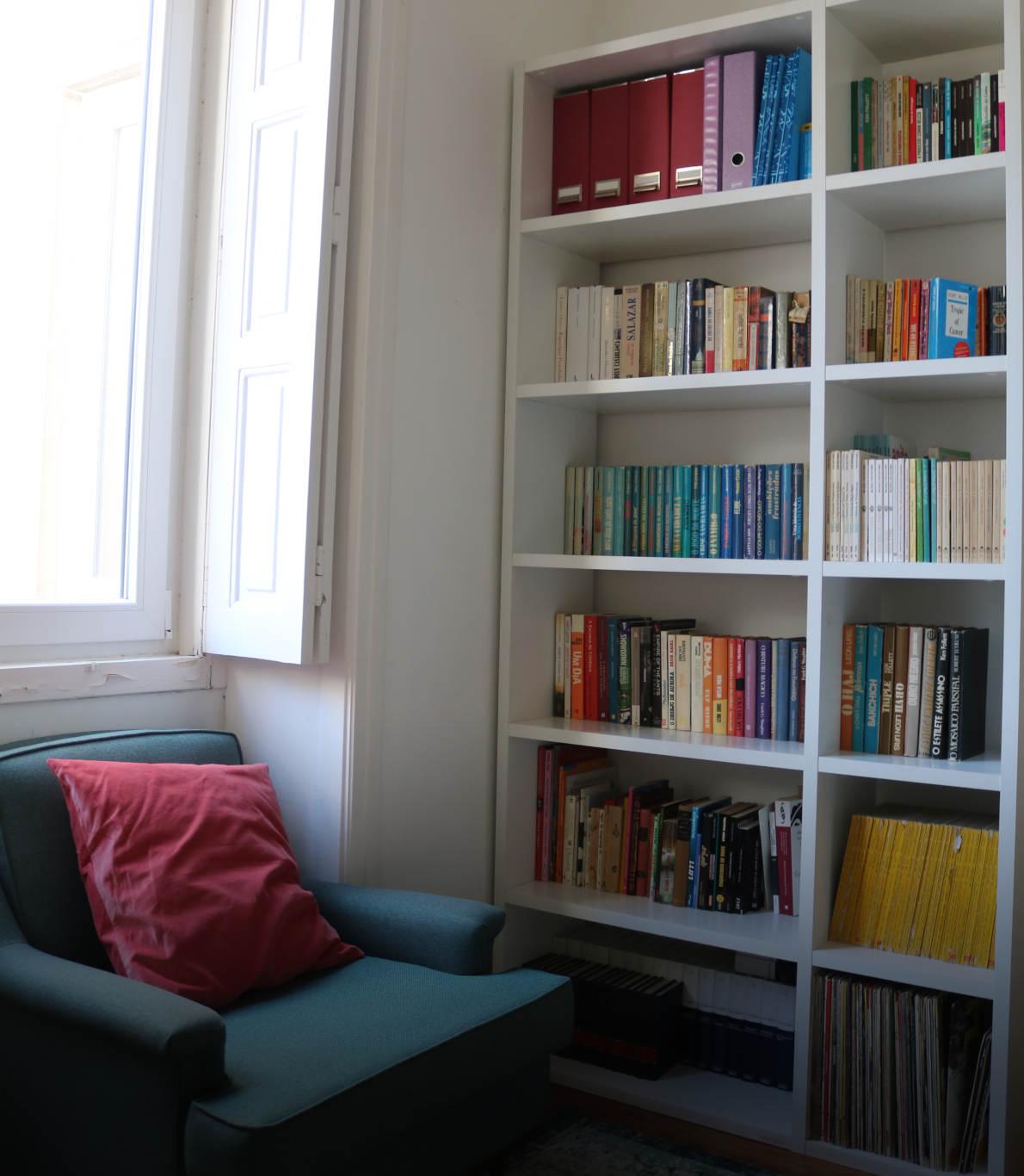 Cantinho de um quarto com uma estante cheia de livros coloridos e um sofá verde