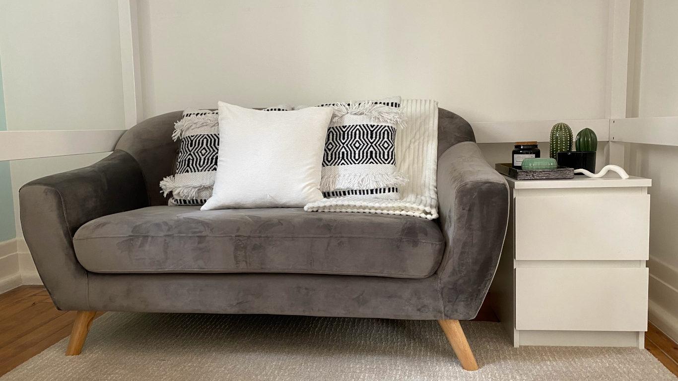 Espaço confortável com um sofá de veludo cinzento revestido de almofadas e uma manta brancas