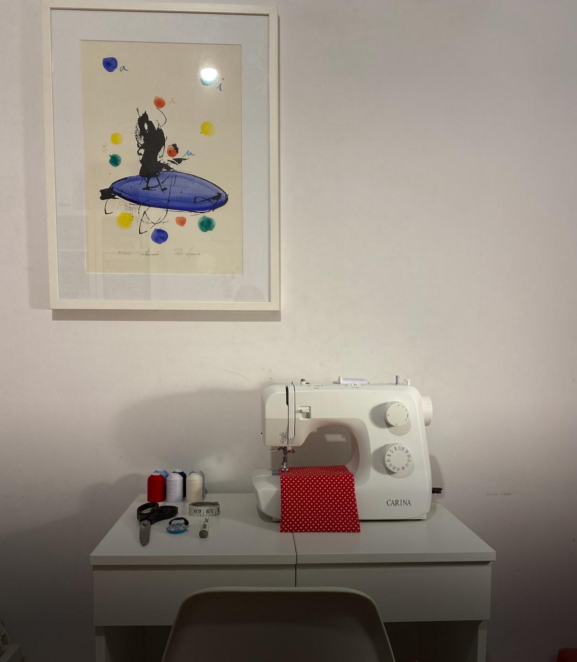 Cantinho da costura com uma máquina própria para a atividade e o material de trabalho