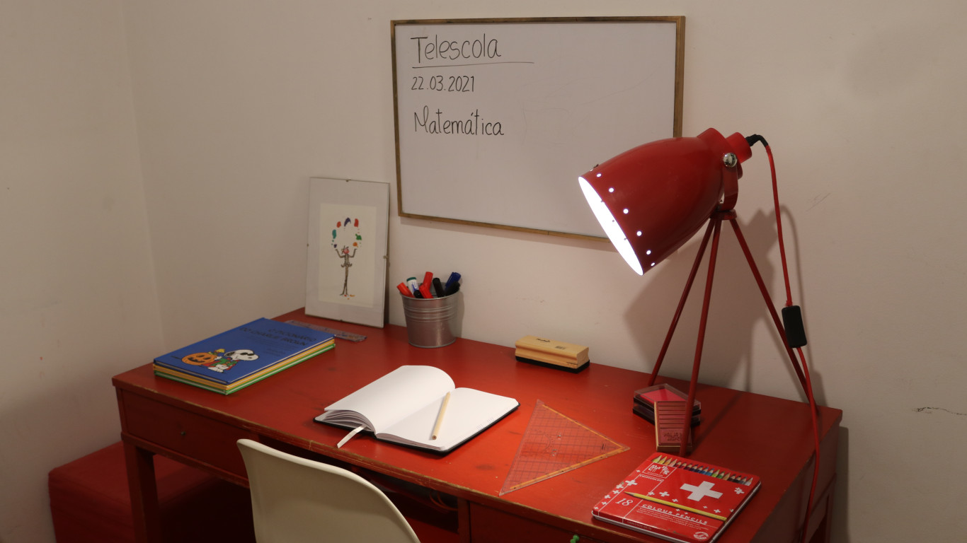 Espaço para Telescola com uma mesa e candeeiro encarnados e vários materiais escolares