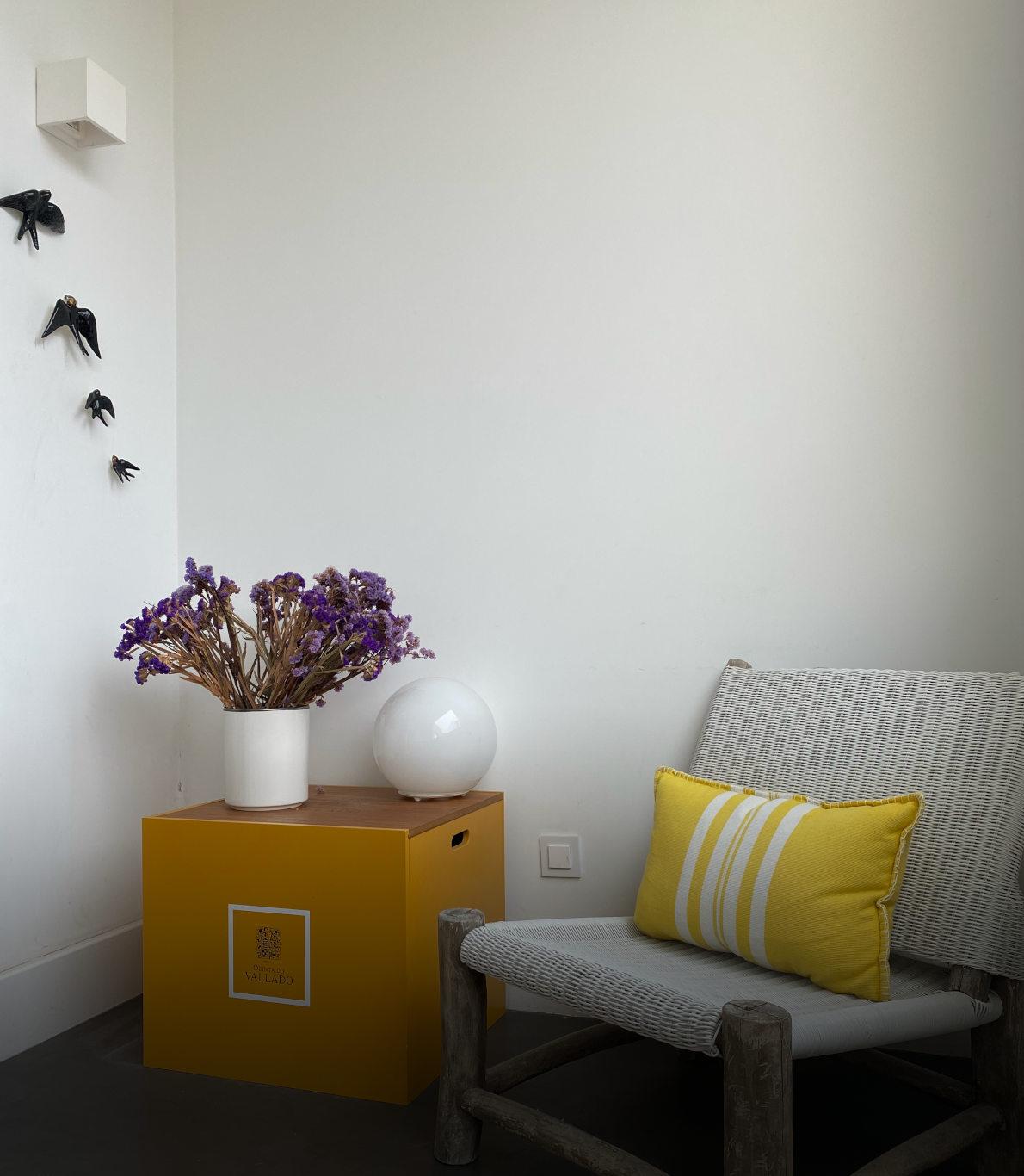 Cantinho de uma varanda exterior com uma cadeira branca e uma mesa ao lado