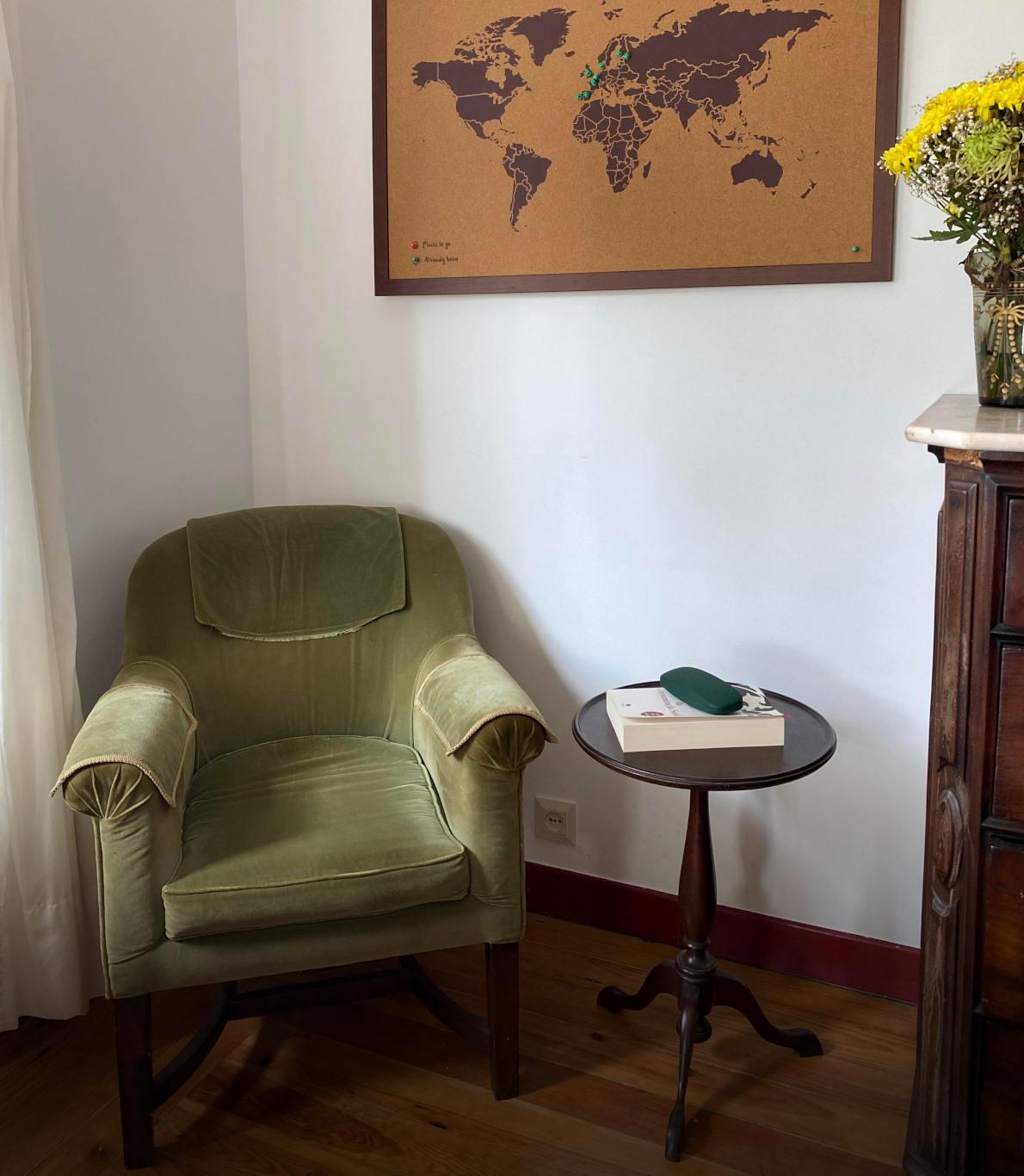 Cantinho para a leitura com uma cadeira restaurada verde e uma mesinha de apoio