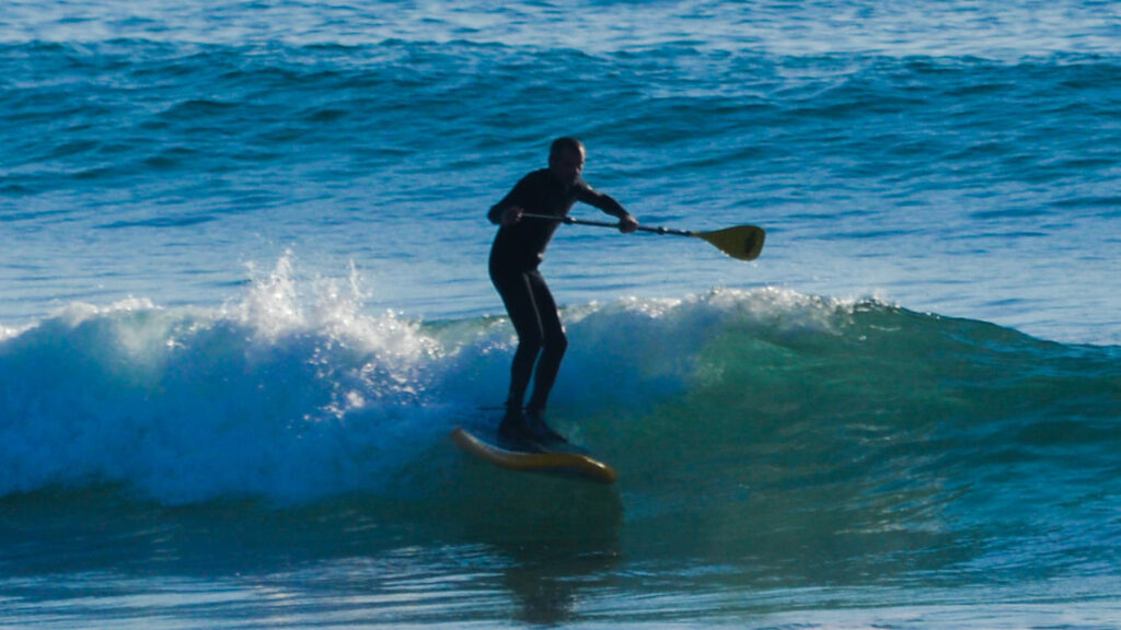Homem com fato preto a fazer paddle com uma prancha e um remo com o mar de fundo