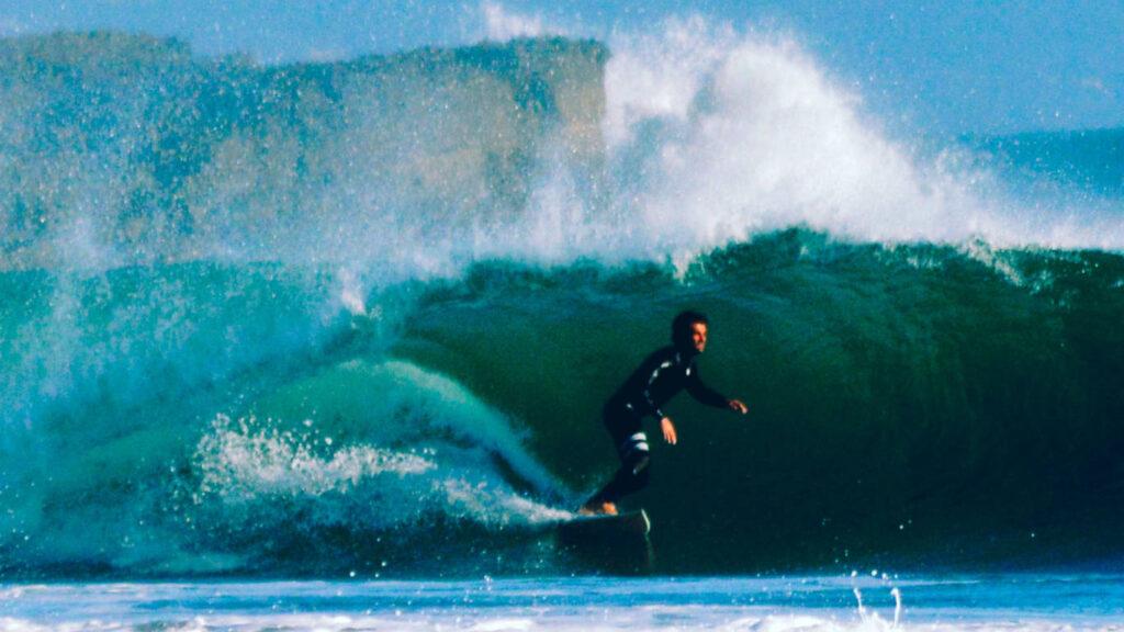 Surfista a surfar uma onda com um fato de surf preto