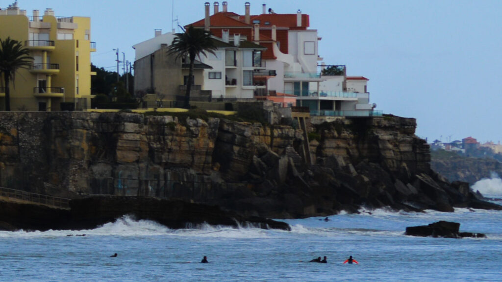 Jovens surfistas apanham ondas no mar enquanto ao fundo existe um prédio amarelo e um prédio branco, as ondas batem nas rochas