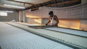 Homem a fabricar t-shirt numa paleta de tecidos