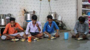 Três homens a comer no chão da fábrica onde trabalham.