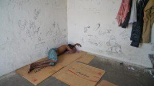 Homem a dormir em cima de um cartão no seu ambiente de trabalho.