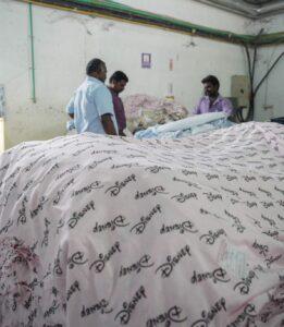 Três trabalhadores na fábrica ao é de tecidos