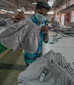 Adolescente a fabricar calções e etiquetar para a marca Primark.