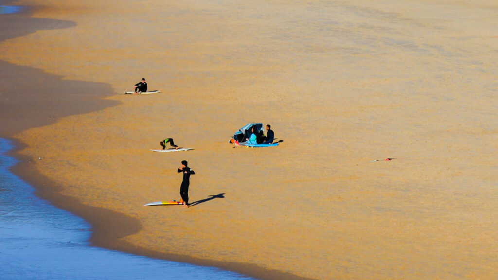 Jovens preparam-se para surfar fazendo um aquecimento no areal em cima das suas pranchas a ver encontra-se um casal debaixo de um guarda – sol azul