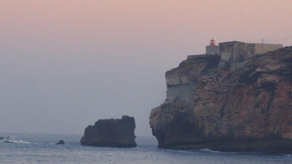 Ao fundo vê-se o mar e as rochas, assim como também se vê um farol