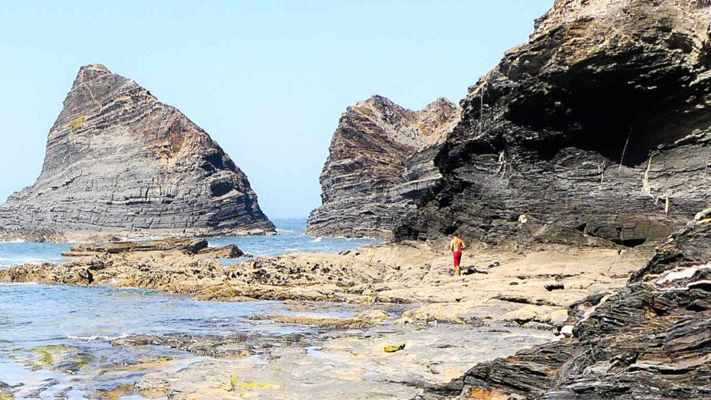 Rochas gigantes no mar e um rapaz com calções vermelhos a passear