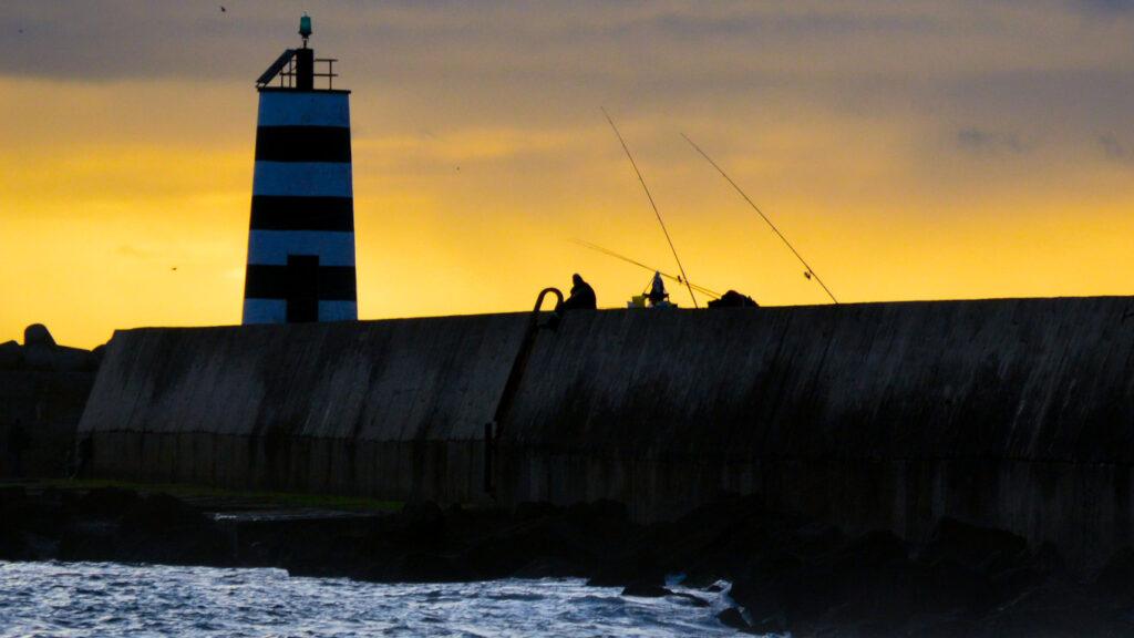 Pessoas a pescar com canas de pesca ao pôr do sol ao fundo está um farol e as ondas
