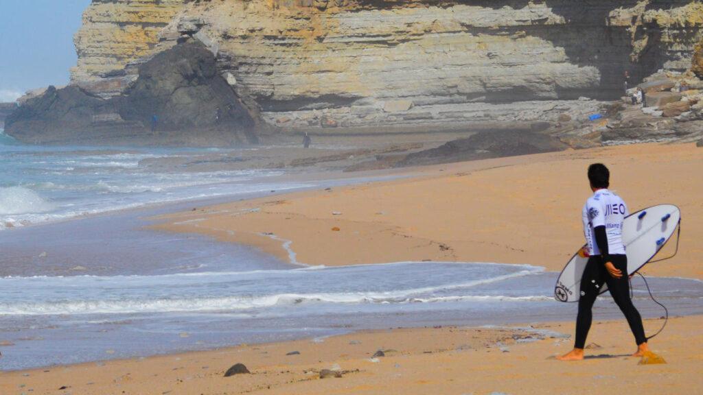 Surfista com t-shirt azul e branca da MEO dirige-se para o mar com uma prancha na mão