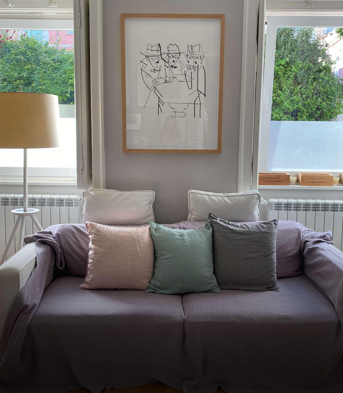 Canto de uma sala de estar com um sofá branco revestido de almofadas coloridas e uma manta lilás por cima
