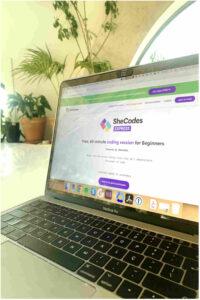 Computador portátil em cima de uma mesa com o website da SheCodes aberto e plantas no background. Imagem do arquivo © SheCodes