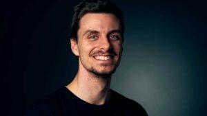 Homem a sorrir para imagem de camisola preta e num fundo escuro e profissional