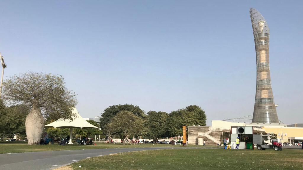 Jardim com vários arbustos e árvores. Ao lado direito é o hotel The Torch
