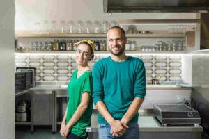 Rapariga e rapaz sorriem na cozinha do seu restaurante, com camisolas verdes que simbolizam o conceito do seu restaurante 100% sustentável.