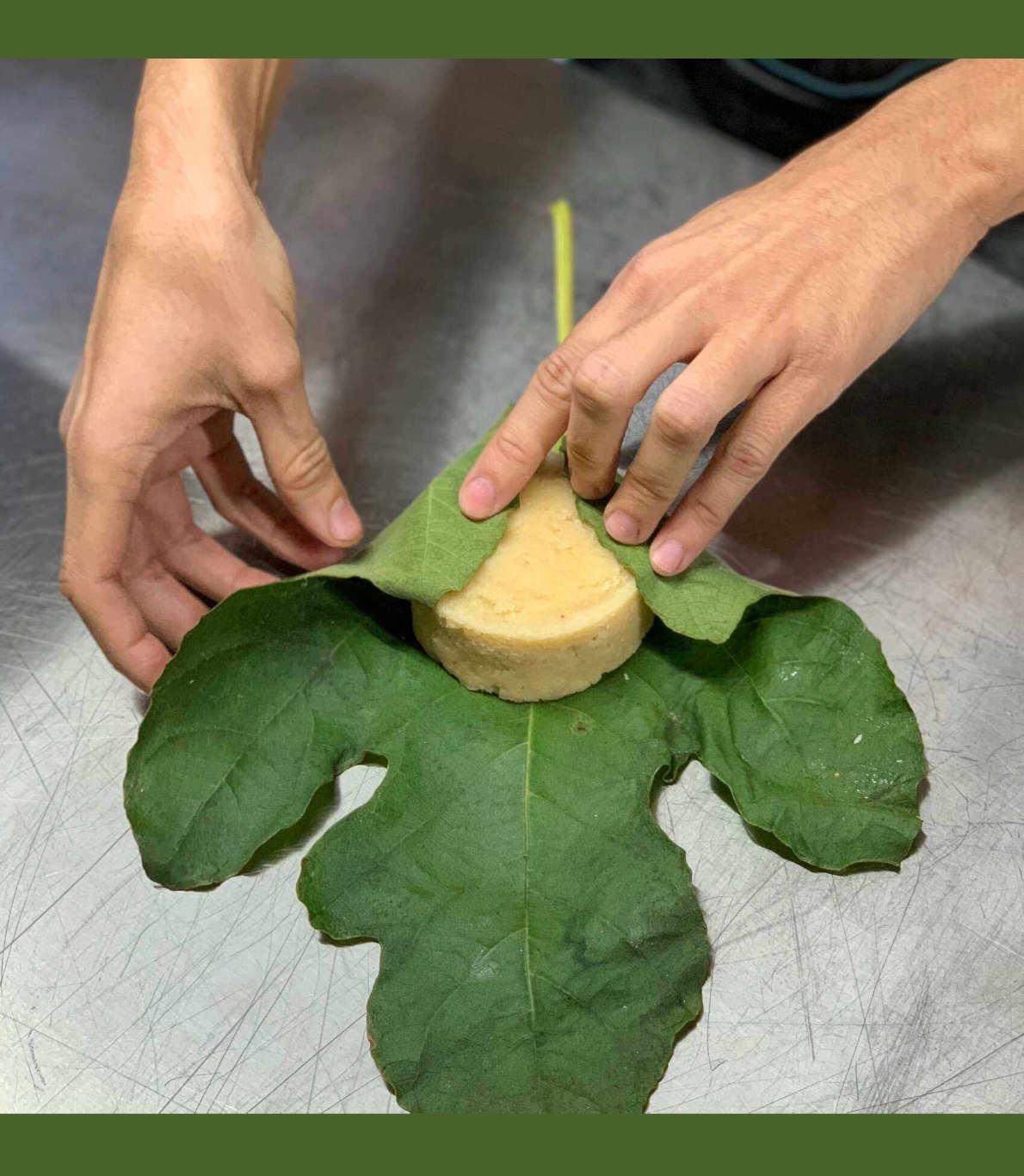 Indivíduo a embalar um queijo vegan com uma folha de couve