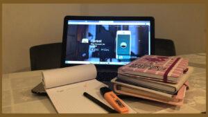 Computador com a aplicação da Forest ligada, em cima de uma mesa com uma agenda, documentos e revistas.