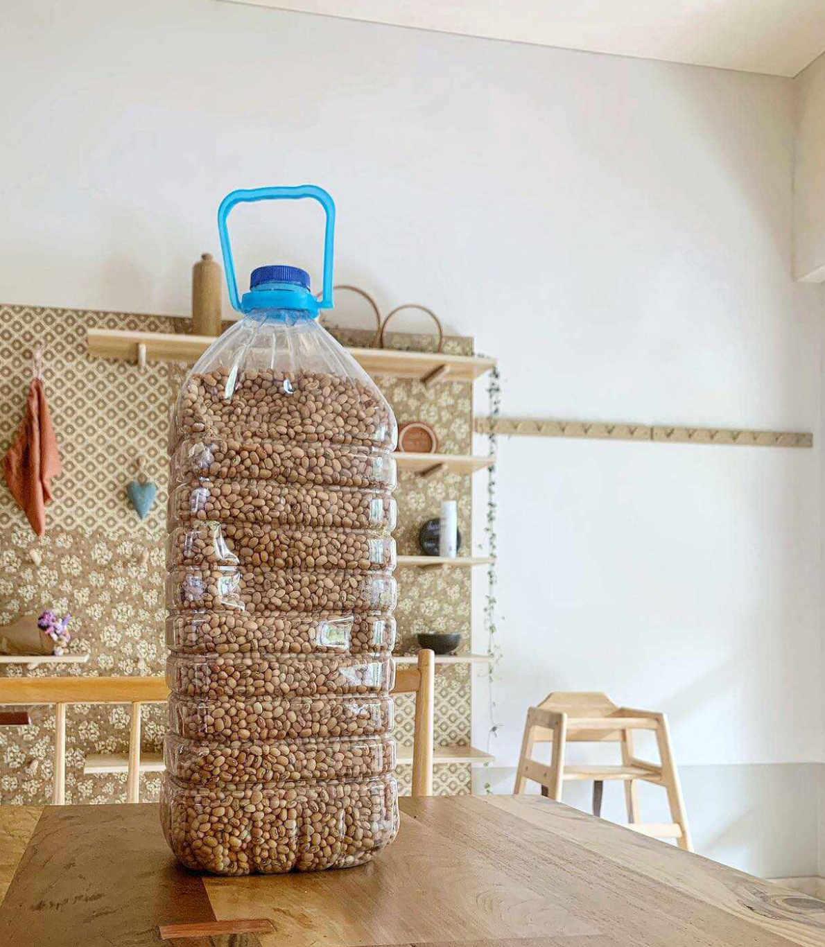 Garrafão com grão biológico em cima de uma mesa, no restaurante dos Kitchen Dates, onde ainda vemos vários utensílios e a decoração deste espaço.