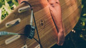 Homem a segurar uma prancha de surf de madeira