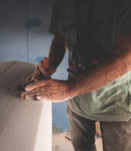 Carpinteiro a trabalhar a superfície de madeira de uma prancha de surf