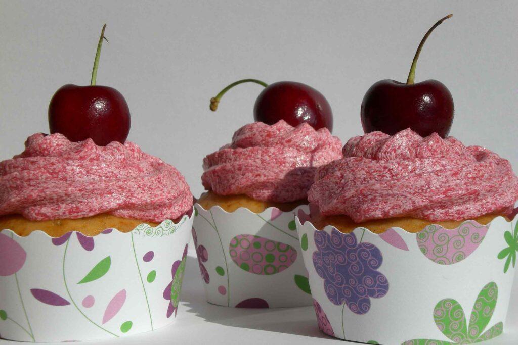 Cupcakes vegan de baunilha e néctar de agave com cobertura de cereja sevidos em formas brancas com flores e formas abstratas rosas, verdes e roxas.