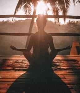 mulher a meditar sentada numa varanda de madeira com o nascer do sol