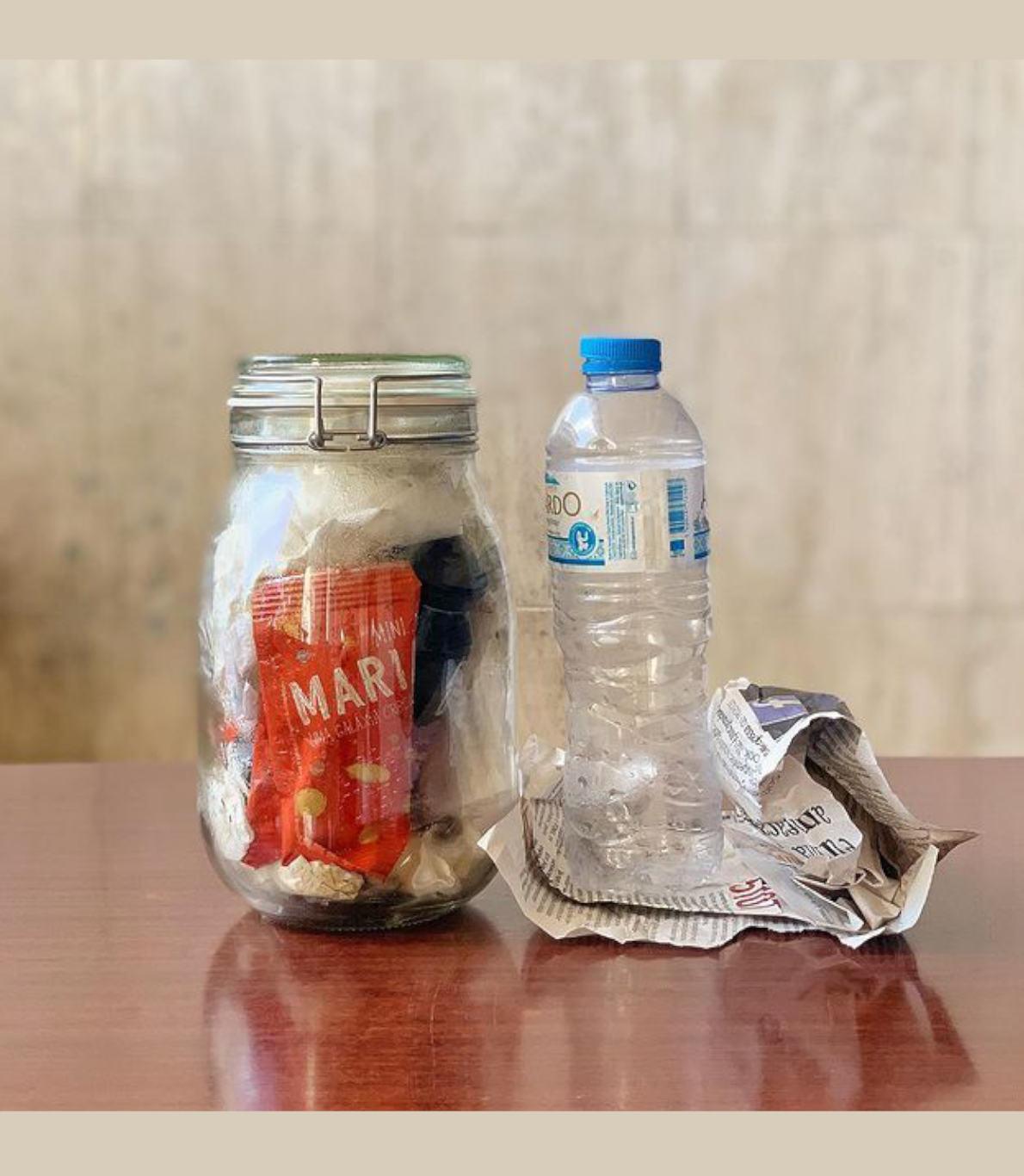 Frasco com resíduos de lixo dos clientes lá dentro. Garrafa de plástico vazia em cima de um pedaço de jornal.