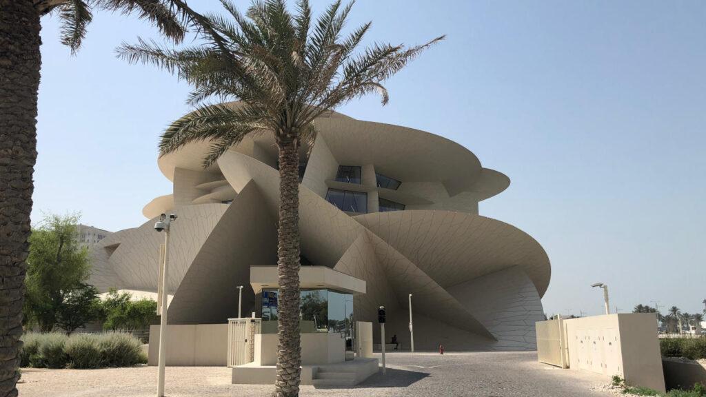Edifício do Museu Nacional do Qatar e a sua respetiva entrada com uma palmeira.