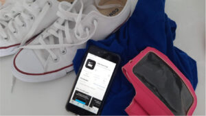 Telemóvel com a aplicação do Nike Run Club ligada, juntamente com ténis, camisola e objeto para a prática de exercício físico.