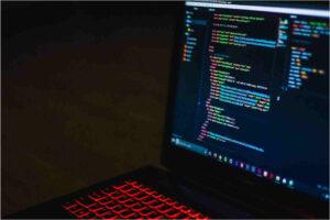 Computador preto com botões iluminados a vermelhos com texto de hmtl no ecrã.