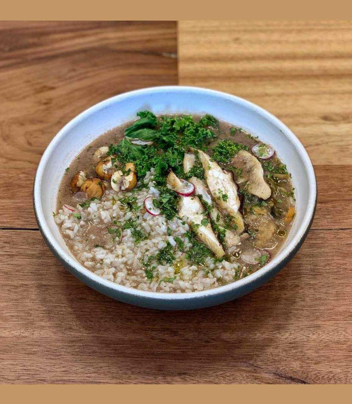 Prato de comida 100% proveniente de vegetais, em cima de uma mesa de madeira. Contém cogumelos shiitakke, arroz e ervas.