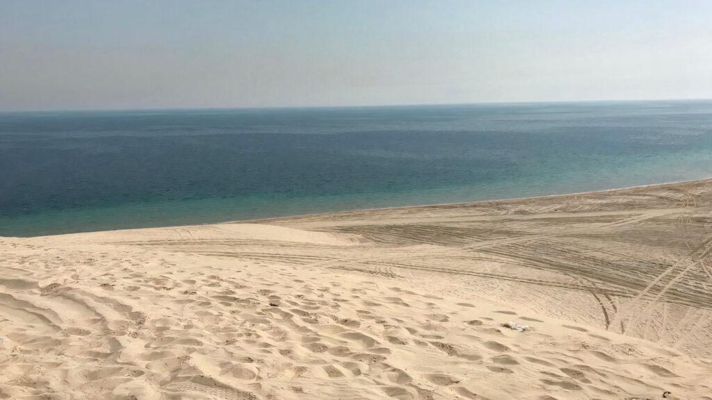 Deserto num primeiro plano e, mais ao longe, o mar.