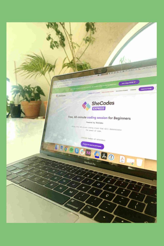 Computador portátil em cima de uma mesa com o website da SheCodes aberto e plantas no background.