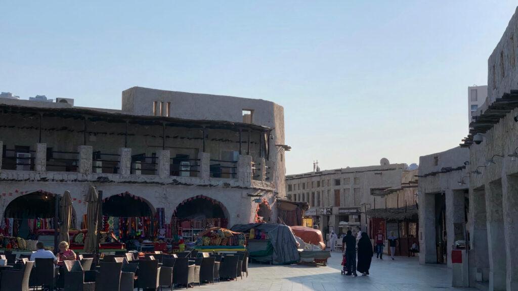 Construção tradicional do Souq Waqif e bancas com tapetes e tecidos à venda e algumas cadeiras para uso das pessoas.