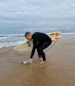 Surfista a apanhar uma garrafa de plástico do mar enquanto segura a prancha com o outro braço