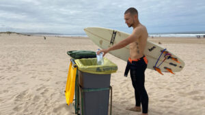 Surfista a reciclar uma garrafa de plástico na praia, enquanto segura a prancha de surf