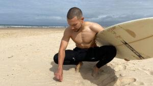 Surfista agachado a apanhar uma beata de cigarro da areia, segurando uma prancha de surf