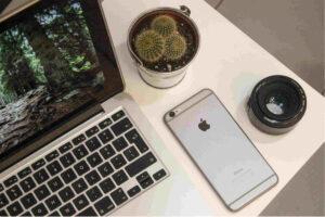 Computador junto de um computador ambos de cor cinzenta em cima de uma mesa com uma lente de camara e um vaso.