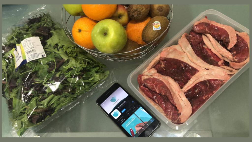 Telemovél com a app da To Good to Go em cima da mesa com a comida recolhida, entre ela carne, alface e frutas