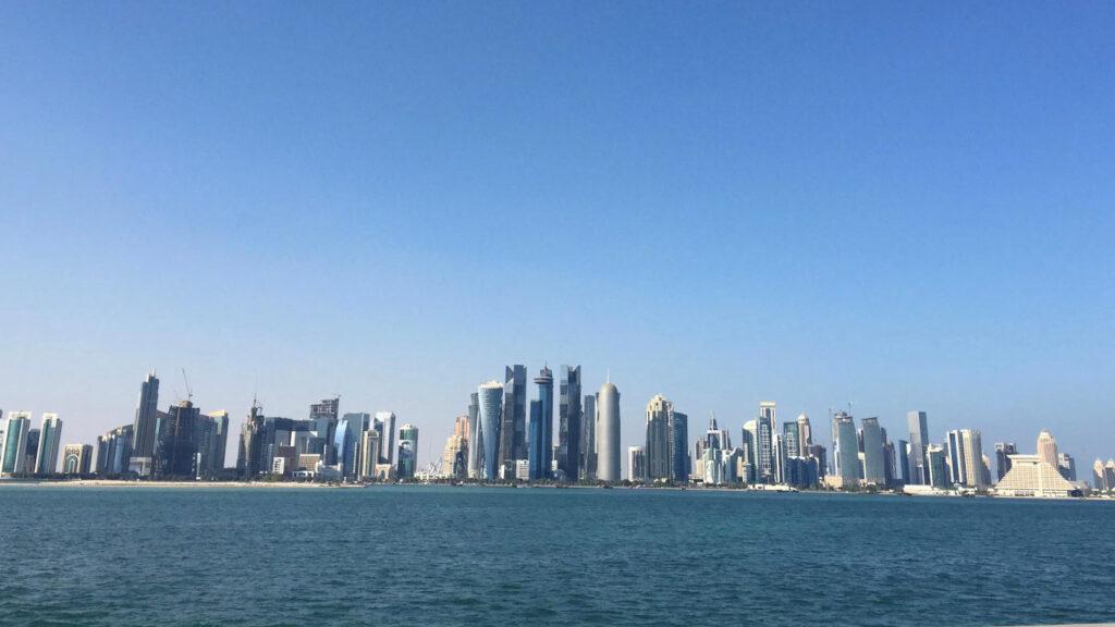 Mar em primeiro plano e de seguida inúmeros edifícios bastante altos que constituem West Bay.
