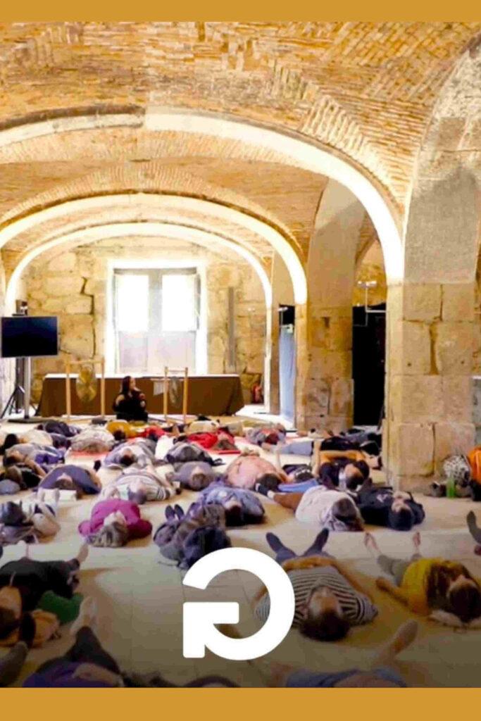 Conjunto de pessoas a meditar deitadas no chão no contexto de um workshop