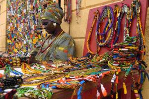 Uma comerciante senegalesa de vestes coloridas na sua banca de venda de artesanato e produtos de bijuteria