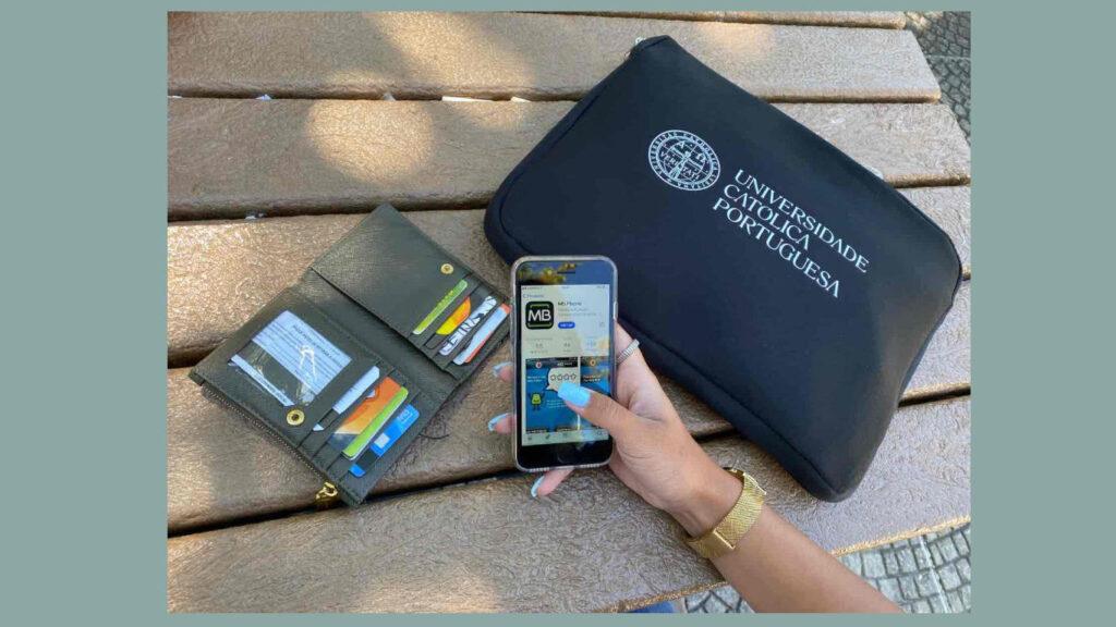 Rapariga com relógio dourado, numa mesa, a a utilizar a app do MB Phone no telemóvel ao lado da sua carteira verde e da pasta da Universidade Católica Portuguesa.